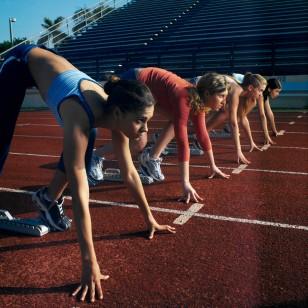 Four Female Athletes (18-21) in Starting Blocks Awaiting the Race Start